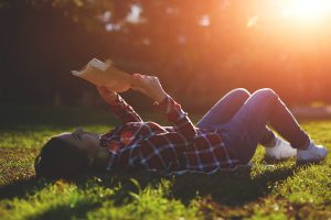 A young woman lying on the grass and reading a book lovely young girl reading a book while lying in a field of grass