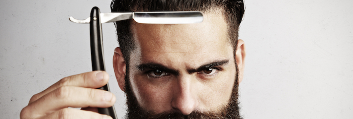 Portrait of bearded man with vintage straight razor